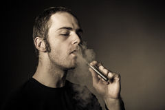Man smokes electronic cigarette Royalty Free Stock Photography