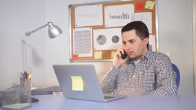 A man smokes an electronic cigarette in an office room, looking at a laptop stock video footage