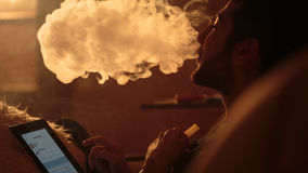 Man smokes a hookah and uses tablet. Young man smokes a hookah and uses tablet Royalty Free Stock Images