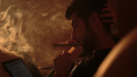 Man smokes a hookah and uses tablet. Young man smokes a hookah and uses tablet Stock Images