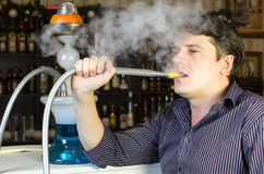 Man smokes a hookah Stock Image