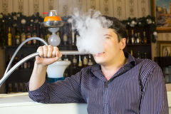Man smokes a hookah Royalty Free Stock Image