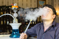 Man smokes a hookah Stock Photos