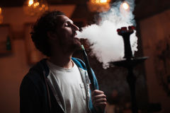 Man smokes  hookah Royalty Free Stock Image