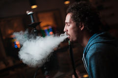 Man smokes  hookah. Young man smokes a fragrant oriental hookah Royalty Free Stock Photos