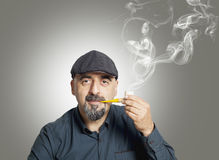 The man smokes a pipe Royalty Free Stock Photo