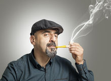 The man smokes a pipe. On gray background Royalty Free Stock Photo