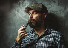 Man smokes a pipe standing near the wall Stock Photos