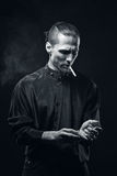 Man smokes. Portrait of smoking man with a cigarette in his hand on a dark background shot in studio Stock Photography