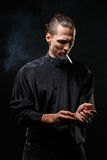 Man smokes. Portrait of smoking man with a cigarette in his hand on a dark background shot in studio Royalty Free Stock Photography