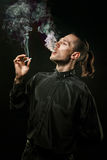 Man smokes. Portrait of smoking man with a cigarette in his hand on a dark background shot in studio Royalty Free Stock Photo