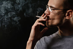 Man smokes. Portrait of smoking man with a cigarette in his hand on a dark background shot in studio Stock Photo