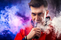 Man smokes a vape. A man smokes a vape, lets steam, studio, colored smoke Stock Photos