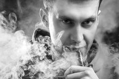Man smokes a vape. A man smokes a vape, lets steam, studio, colored smoke. Black and White Stock Images