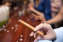 Man smoking cigar, shallow focus Stock Photos