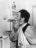Man smoking cigar and shaving Royalty Free Stock Photo
