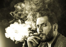 Man Smoking Cigar surrounded by Smoke Stock Images