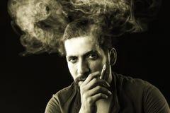 Man Smoking Cigar surrounded by Smoke Royalty Free Stock Photos