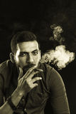 Man Smoking Cigar surrounded by Smoke Stock Photography