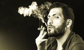 Man Smoking Cigar surrounded by Smoke Stock Image