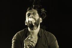 Man Smoking Cigar surrounded by Smoke Stock Photography