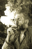 Man Smoking Cigar surrounded by Smoke Royalty Free Stock Images