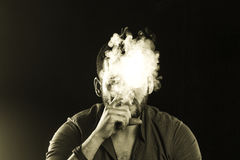 Man Smoking Cigar surrounded by Smoke Stock Photos