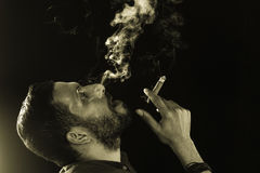 Man Smoking Cigar surrounded by Smoke Royalty Free Stock Photography