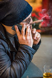 Man smoking a cigar and talking on the phone - side view Royalty Free Stock Photo