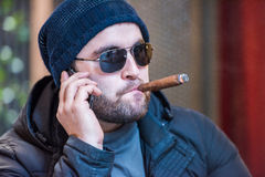 Man smoking a cigar and talking on the phone - side view Stock Photos