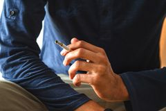 Man smoking cigarette. Close up of a man& x27;s hand holding a cigarette habit smoker tobacco addiction white drug unhealthy background nicotine person young royalty free stock photography