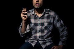 Man smoking cigarette in the dark Stock Photo
