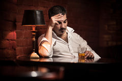 Man smoking cigarette and drinking whiskey. In bar Royalty Free Stock Photography