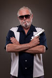 Man smoking a cigarette and holding handgun Royalty Free Stock Photography