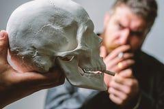 Man smoking cigarette near human skull symbol of death. Harmful habits. Smoking cause health damage and death. Destroy. Your health. Smoking is harmful. Habit stock photography