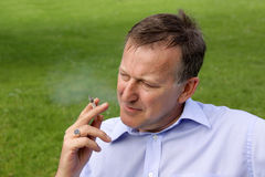 Man smoking a cigarette outdoors Stock Photos
