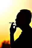 A man smoking cigarette over golden sunset Stock Images