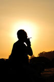 A man smoking cigarette over golden sunset Stock Photography