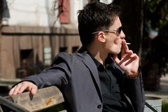 Man smoking a cigarette sitting on a bench Stock Photo