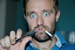 Man smoking e-cigarette, regular cigarette. Make funny face Royalty Free Stock Photo