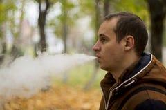 Man smoking electronic sigarette outdoor. Man smoking electronic sigarette in the forest Stock Photography