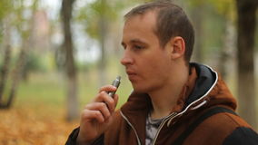 Man smoking electronic sigarette outdoor. Man smoking electronic sigarette in the forest stock video