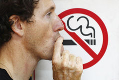 Man smoking a no-smoking sign Stock Photos
