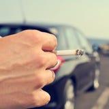 Man smoking in a no traffic road Stock Image