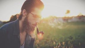 Man smoking pipe in field Royalty Free Stock Image