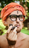 Man smoking pipe in glasses Stock Images