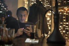 Man smoking pipe of hookah in night cafe Royalty Free Stock Photography