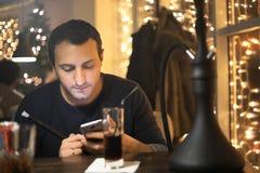 Man smoking pipe of hookah in night cafe Royalty Free Stock Image