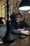 Man smoking pipe of hookah in night cafe. Man smoking pipe of hookah in a night cafe Royalty Free Stock Images