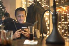 Man smoking pipe of hookah in night cafe Stock Photos